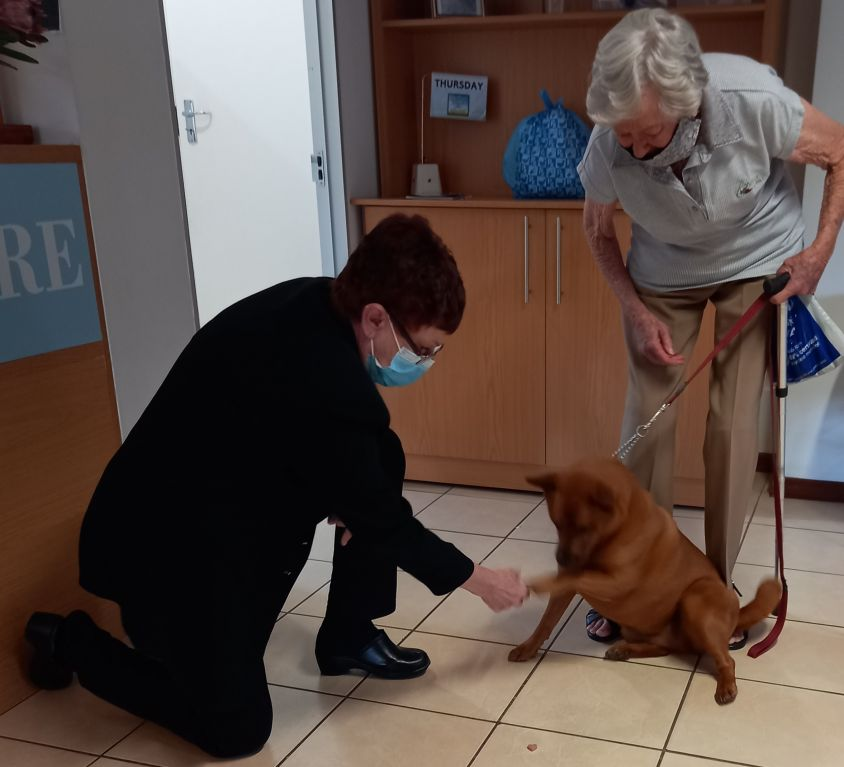 Thornhill-Manor-manager-Esme-Erasmus-standing-in-for-Shirley-Whitehead-who-initiated-the-treat-programme-with-resident-Ann-Raats-and-Hachiko.